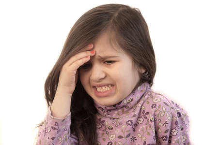 Cute little girl with her hand held to her forehead with painful expression showing headache