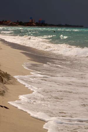 glistening: El relucir playa del Caribe a orillas del mar con vista al mar turquesa y cielo tormentoso en el fondo Foto de archivo
