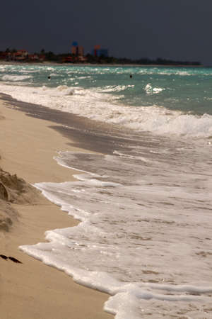 glistening: Glistening Caribbean beach at seashore with turquoise ocean and stormy sky in the background Stock Photo