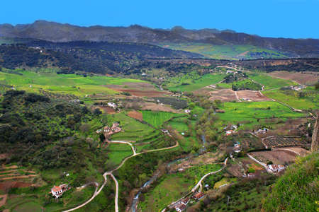 Birds eye view of the valley in Ronda, Spain with mountainous terrain in the background photo