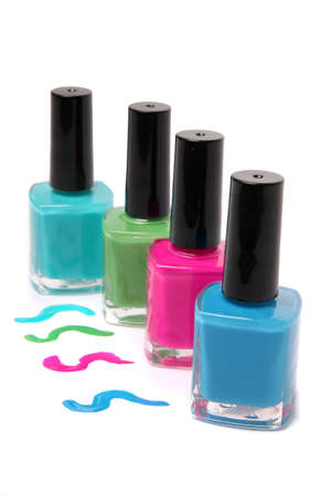 Nail polish bottles and spots in bright spring or summer colors in light blue, pink and green on a white background 免版税图像