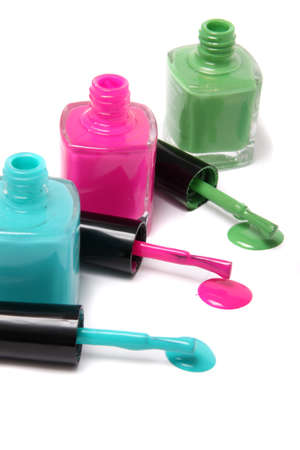 Nail polish bottles and spots in bright spring or summer colors in light blue, pink and green on a white background Stock Photo
