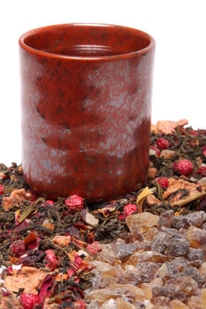 sweeten: Cup of tea with dried loose berry mix beside brown rock sugar to sweeten the beverage Stock Photo