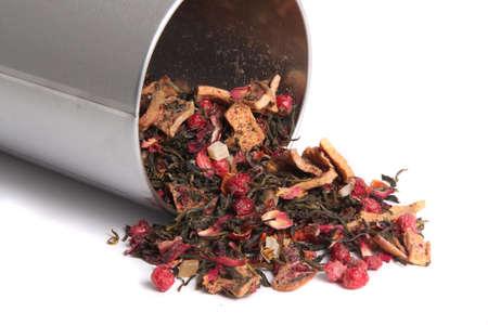 Gedroogde losse gemengde bessen en groene thee thee morsen van een tin klaar om te steil en brouwsel op een witte