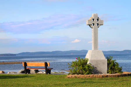 memorial cross: Banco de madera vacío por un memorial de la cruz céltica con una vista al mar de la Bahía de Fundy en St. Andrew by the Sea, Nueva Brunswick, Marítimos, Canadá