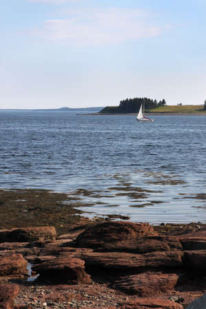 maritimes: Rocky shoreline beach and sailboat in the background in St. Andrews, New Brunswick, Maritimes, Canada Stock Photo