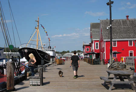 fisheries: August 5. 2014, Lunenburg, Nova Scotia: People hanging out on the boardwalk along the Fisheries Museum of Lunenburg, Nova Scotia