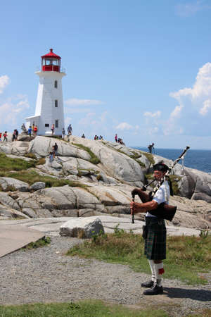 August 6, 2014, Peggys Cove, Nova Scotia: Bagpiper playing music in front of the lighthouse in touristic Peggys Cove, Nova Scotia, Canada