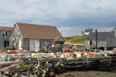buoys: Fishing shacks with colorful buoys along the Atlantic Shore in Peggys Cove, Nova Scotia, Canada, Stock Photo