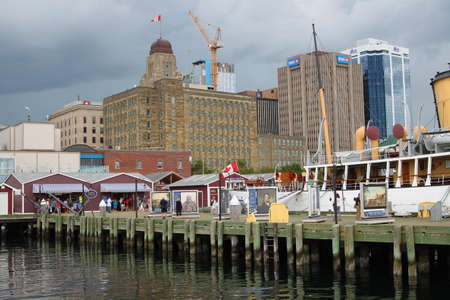 Halifax, Nova Scotia, Canada, August 9, 2014: Touristic harbor waterfront with shops and tourist, gray skies in the background in Halifax, Nova Scotia