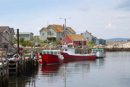 Coastal village of Peggys Cove, Nova Scotia, Canada, showing seaside shacks, fishing boats, and houses along the coast