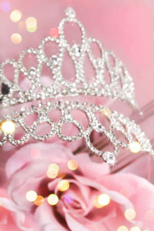 Beauty queens glittery crown on pink background with roses and gold bokeh  Stock Photo