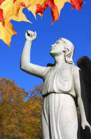 Statue of Angel looking towards the sky or heaven with arm raised up in faith or hope, at a cemetery in Montreal, Quebec with colorful maple autumn leaves photo