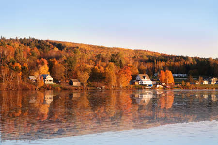 Autumn countryside of New Brunswick Canada along the Saint John River with reflections on the water during sunset