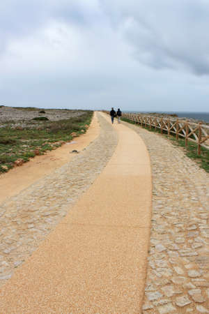 handholding: Couple walking on a long path with dark stormy sky above Stock Photo