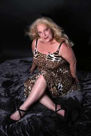 Sexy mature blonde woman in her mid fifties posing on black velvet background Standard-Bild