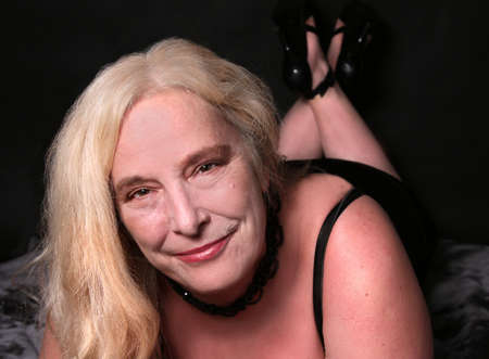 bare women: Blonde woman in her mid fifties laying doing a sexy pose on a black velvet background showing high heels