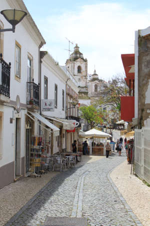Lagos: Lagos, Portugal, April, 15 2014: A popular cobblestone covered street for tourists in Lagos with restaurants, and souvenir shops with church in background