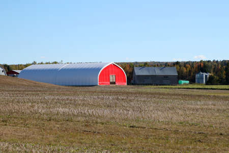 maritimes: Red barn in dry agriculture land during the fall season in a rural area in New Brunswick, Maritimes, Canada Editorial