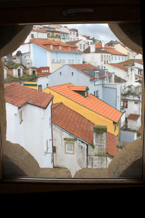 cluster house: View of red shingled rooftops in Coimbra, Portugal looking through a window