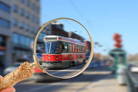 investigative: Magnifying glass looking in on a streetcar, the transportation in downtown Toronto, Canada with motion blur