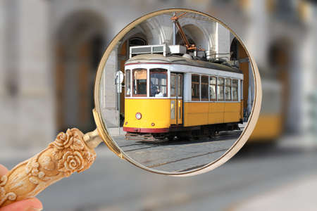 streetcar: Magnifying glass focusing on yellow streetcar or tram in Lisbon, Portugal, Europe Editorial