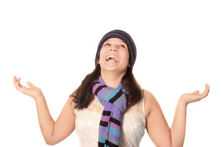 stretched out: Girl wearing wool hat and scarf happily smiling with arms stretched out and looking up towards sky as if catching something