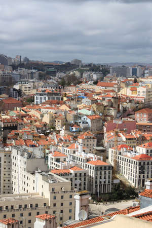 cluster house: Cluster of buildings of Lisbon city, Portugal under cloudy sky with sun shining through