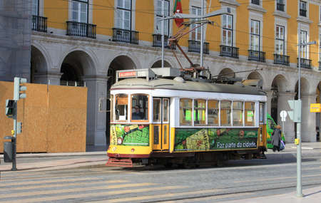 streetcar: LISBON,PORTUGAL,APRIL 23,2014: Historic yellow tram or streetcar on the cobblestone streets of Alfama, Lisbon, Portugal