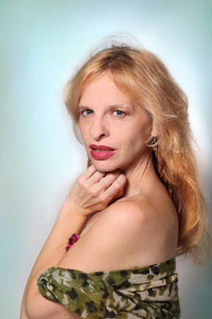 Beautiful blonde woman in her late thirties looking at the camera with shoulder exposed