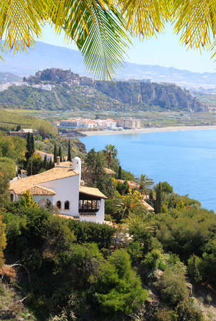 motril: House on a cliff along Costa del Sol with Motril in the background and palm leaves making a border, Andalucia, Spain Editorial