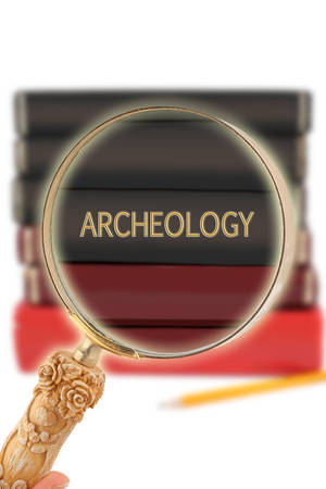 archaeology: Magnifying glass or loop looking on an educational subject - Archaeology Stock Photo