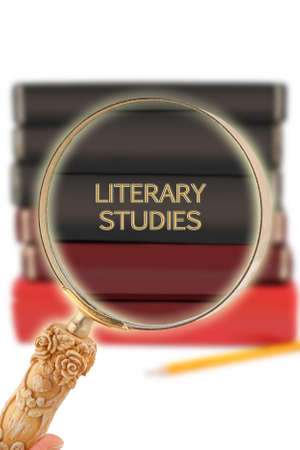 Magnifying glass or loop looking on an educational subject  - Literary Studies Stock Photo