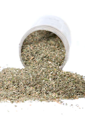 Dried green catnip for cats spilling from container on a white background