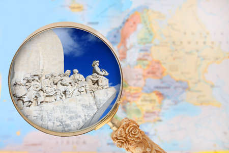 Looking in on the Explorers monument in  Portugal with a magnifying glass or loop with European map in the background