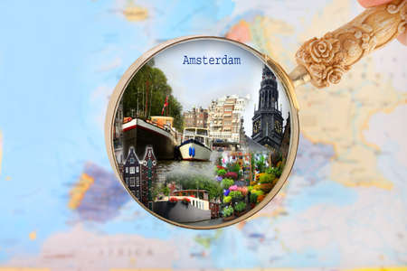 gabled house: Blue tack on map of Europe with magnifying glass looking in on Amsterdam, Netherlands