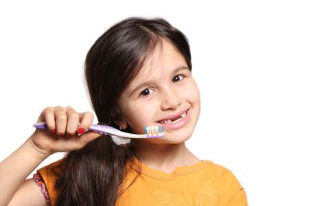top seven: Little seven year old girl shows big smile showing missing top front teeth and holding a toothbrush on a white background Stock Photo