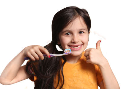 top seven: Little seven year old girl shows big smile showing missing top front teeth and holding a toothbrush with toothpaste and thumbs up on a white background