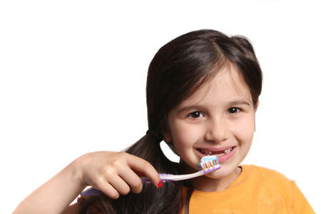 front teeth: Little seven year old girl shows big smile showing missing top front teeth and holding a toothbrush with toothpaste on a white background Stock Photo