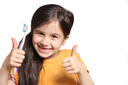 top seven: Little seven year old girl shows big smile showing missing top front teeth and holding a toothbrush with thumbs up on a white background Stock Photo