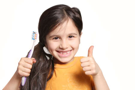 oral: Little seven year old girl shows big smile showing missing top front teeth and holding a toothbrush on a white background Stock Photo