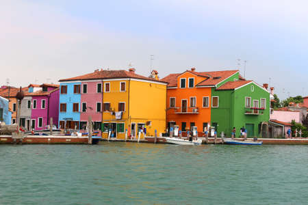 town houses: BURANO,ITALY,June 25, 2015: Colorful fishermens houses along the shore  of the Italian island of Burano, Italy