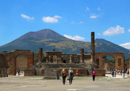 mount: POMPEII, ITALY ,JUNE 27, 2015: People walking along the Forum in Pompeii, with volcano Mount Vesuvius in the background