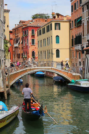 walkway: VENICE, ITALY, JUNE 23, 2015: Tourists take a gondola ride  through a busy canal with colorful houses of Venice, Italy