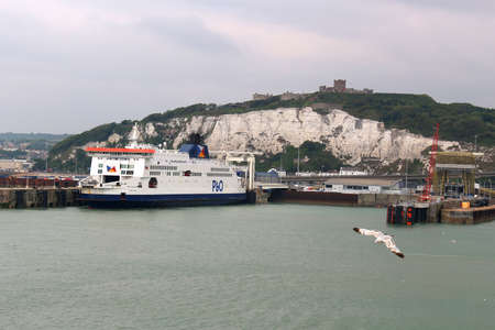 english channel: DOVER, UNITED KINGDOM, JUNE 20, 2015: Ferry boat docked in the Port of Dover in the English Channel, England with seagulls flying around Editorial