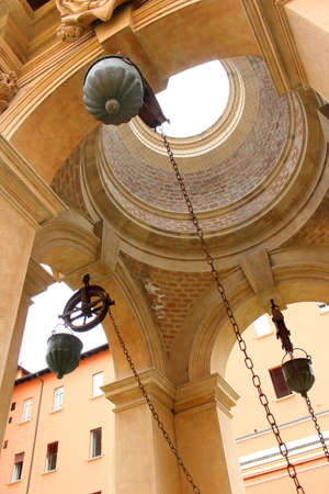 pulleys: Looking up a well in a public square showing its chains, and pulleys in Bologna, Italy