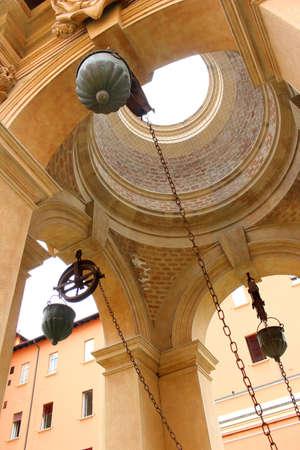 pulleys: Mirando hacia arriba un pozo en una plaza p�blica que lo muestra es cadenas y poleas en Bolonia, Italia Editorial