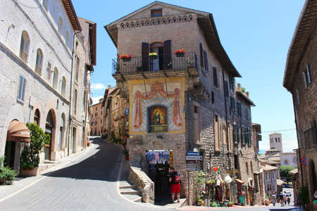 old street: ASSISI, ITALY - JUNE 24, 2014: Hilly Street in the town of Assisi Italy showing souvenir shops for tourists