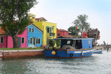 Colorful  houses on the Italian island of Burano with boats moored on the canal