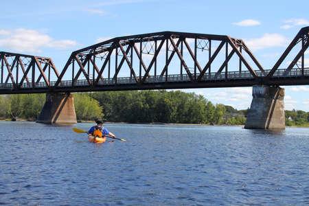 Man kayaking on the Saint John River  in Fredericton, New Brunswick in Atlantic Canada